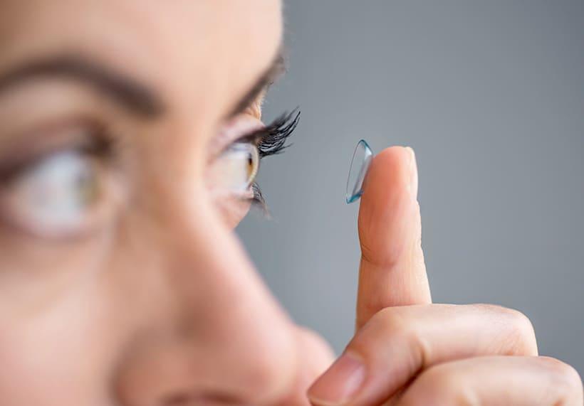 persona colocándose lentes de contacto visualiza