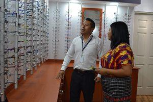 fotografía de la Óptica en centro de visión Chimaltenango, paciente tratando de elegir algún aro mientras un colaborador le indica cuales pueden ser las mejores opciones para ella.