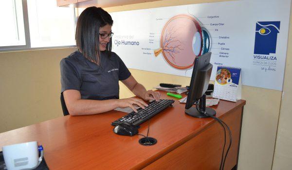 Fotografía de nuestra área de consejería y una de nuestras colaboradoras sentada en su escritorio ingresando datos de un paciente para su cirugía.